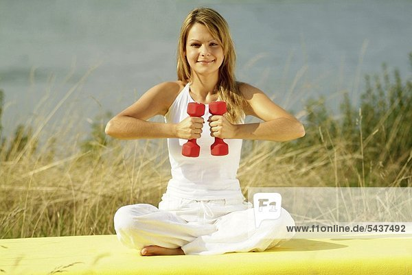Young blond woman sitting on a mat working out with two dumb-bells