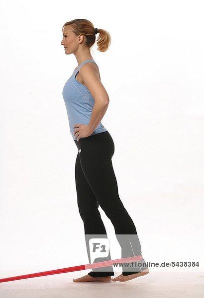 Mobilisation des Bewegungsapparats - gegen Verspannungen und Schmerzen - fördert die Durchblutung   schmiert die Gelenke - Junge blonde Frau kräftigt Ihre Beinmuskulatur mit Hilfe eines Thera-Bands