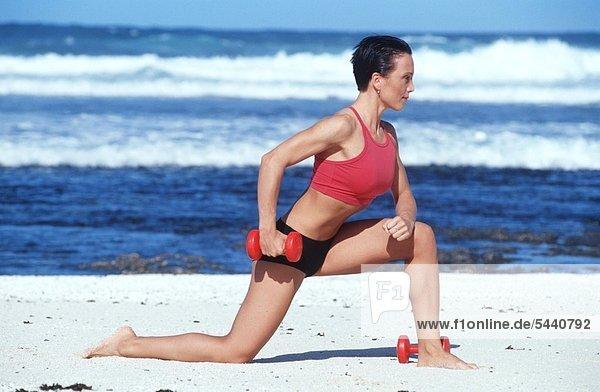 Frau macht mit Hanteln Sport am Strand - im Kniestand Hantel anheben