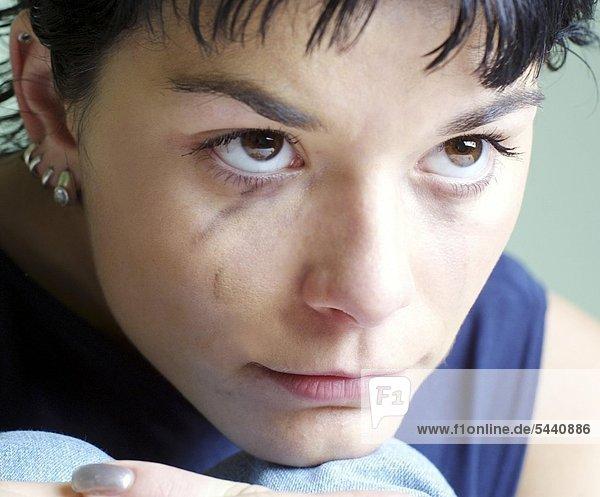 Junge Frau mit verschmierter Wimperntusche im Gesicht