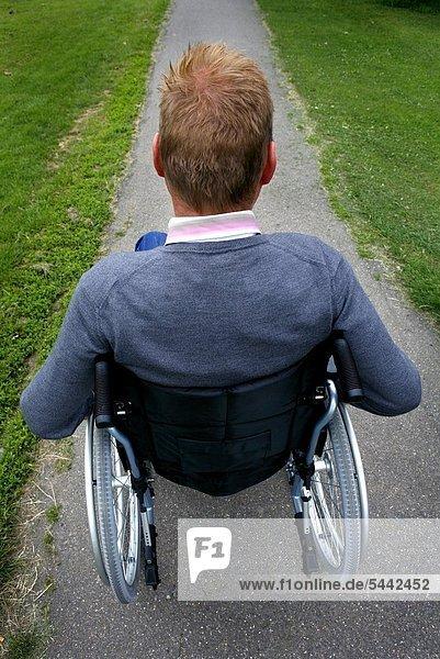 A Man Wheelchair bound  wheeling through a park