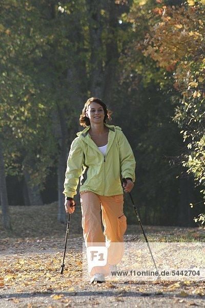 Junge Frau beim Nordic Walking an einen sonnigen Herbsttag Junge Frau beim Nordic Walking an einen sonnigen Herbsttag