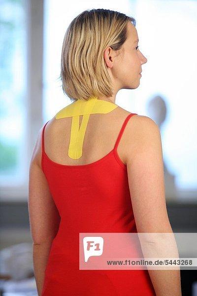 MEDI-TAPING : HWS-Tape an Halswirbelsäule einer jungen Frau