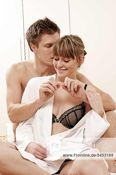 Junges Paar mit Kondom im Bett