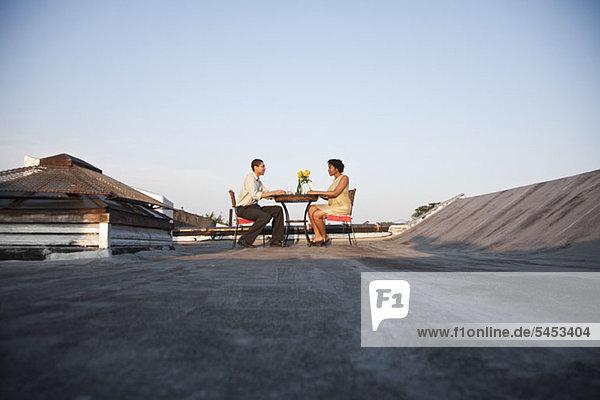 Ein Paar beim Essen auf der Dachterrasse