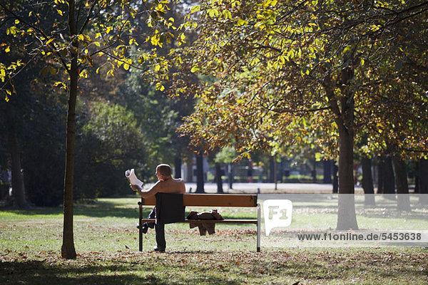 Ein Geschäftsmann ohne Hemd  der eine Zeitung auf einer Parkbank liest.
