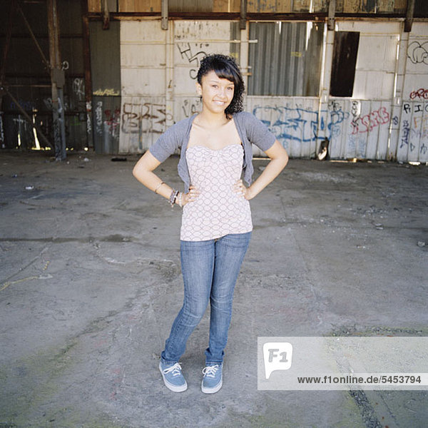 A fashionable teenage girl posing in an urban setting
