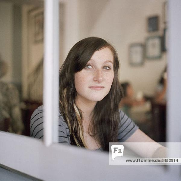 Eine junge Frau  die durch ein Fenster in Kontemplation schaut.