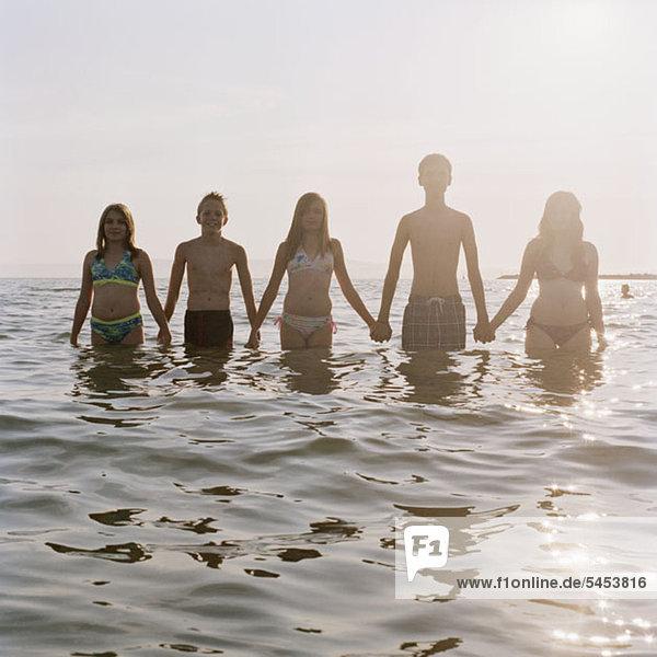 Fünf Freunde halten sich an den Händen  während sie im Meer waten.