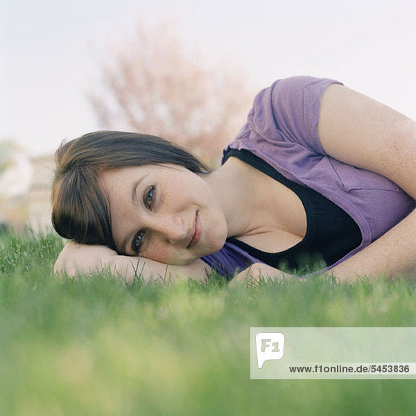 Eine junge Frau  die im Gras liegt.