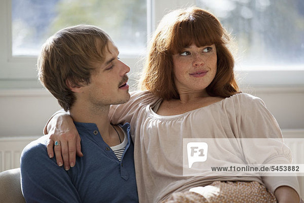 A woman looking away playfully while her boyfriend talks to her