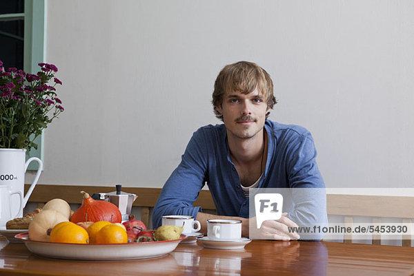 Ein junger Mann beim Frühstück  der in die Kamera schaut.