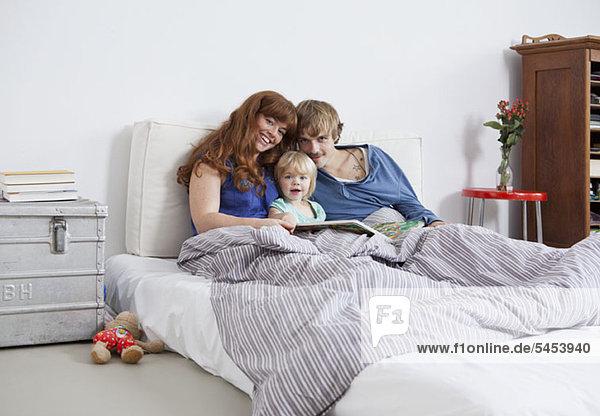 Eine junge Familie im Bett beim Lesen eines Bilderbuches