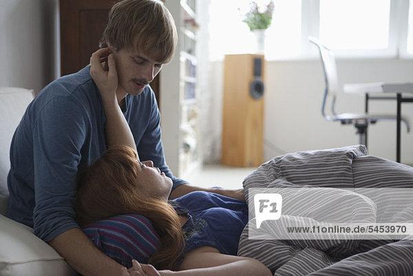 Ein junges Paar  das im Bett liegt und redet und anhänglich ist.