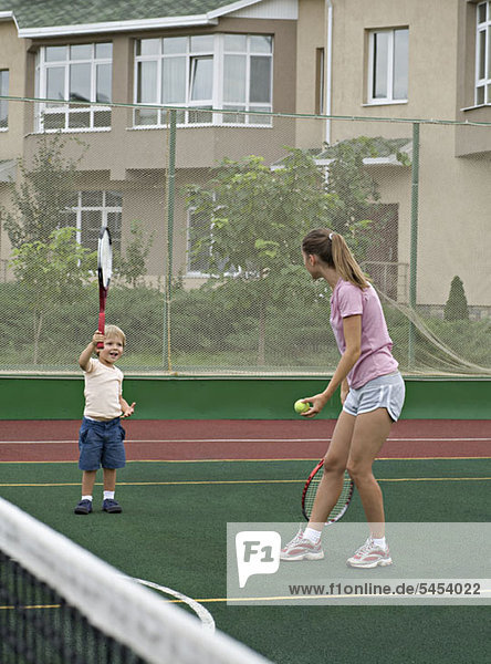 A mother preparing to serve a tennis ball to her young son 1089024