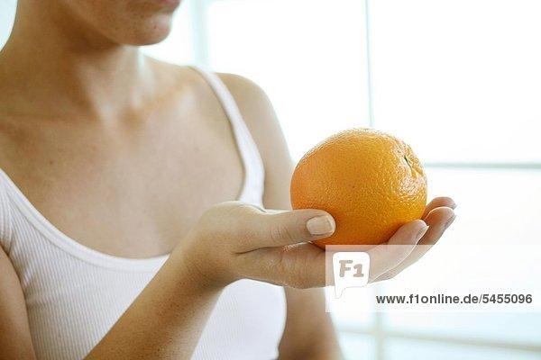 Frau hält eine Orange