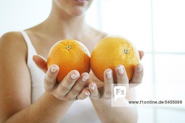 Frau hält zwei Orangen