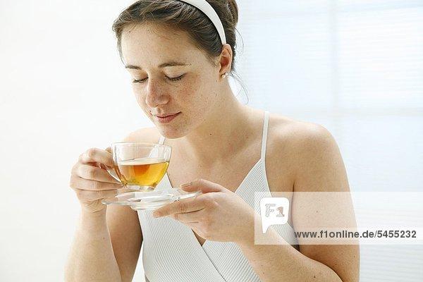 Lächelnde Frau mit einem Glas Tee