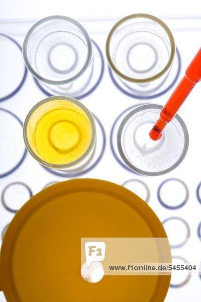 Pipette tropft rote Flüssigkeit in Reagenzglas