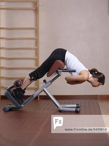 Junge Frau im Fitnessstudio beim Training der Rückenmuskulatur
