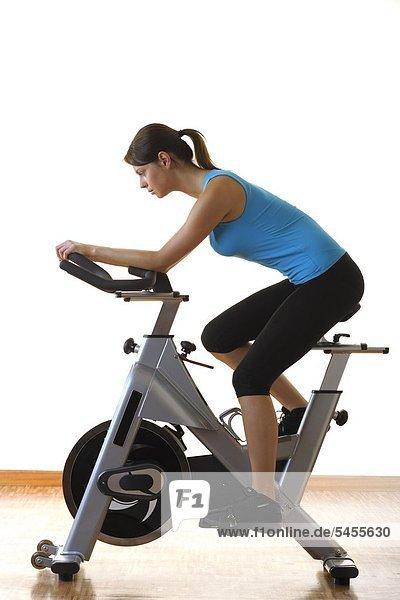 Junge Frau auf einem Hometrainer - Fahrrad