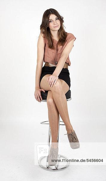 Junge Frau mit beigem Top und schwarzem Minirock  sitzt auf Hocker