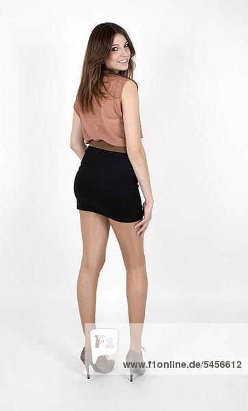 Junge Frau mit beigem Top und schwarzem Minirock