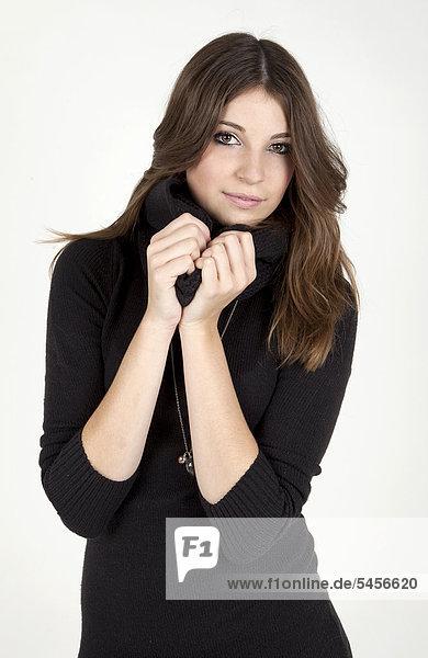 Junge Frau zieht den Kragen ihres schwarzen Pullovers hoch