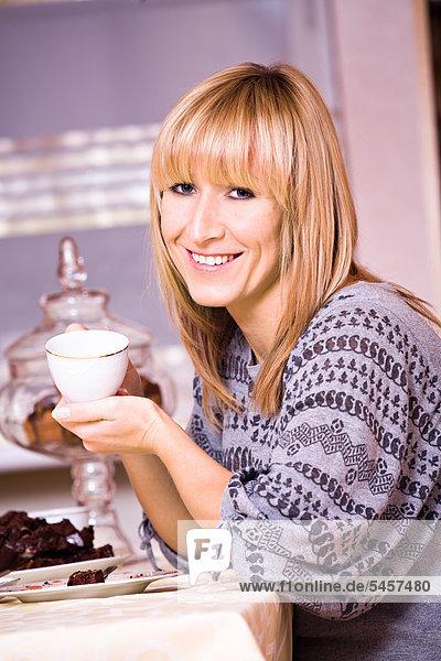 Frau sitzt mit Teetasse und Kuchen in der Küche