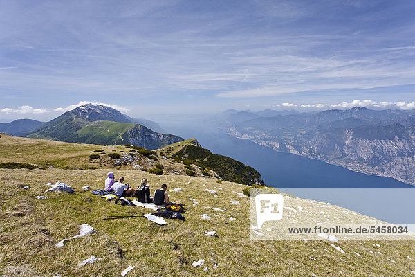 Hikers resting on Monte Altissimo above Nago  Lake Garda below  Monte Baldo at back  Trentino  Italy  Europe