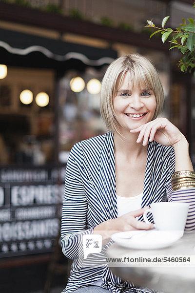 Frau beim Kaffeetrinken im Straßencafé