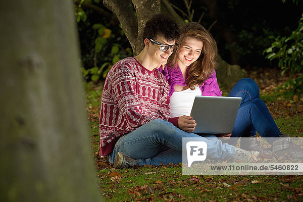 Teenage couple using laptop in park