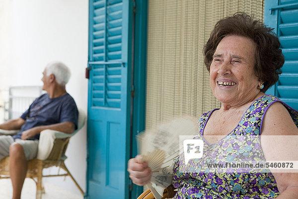 Ältere Frau fächelt sich im Freien auf.