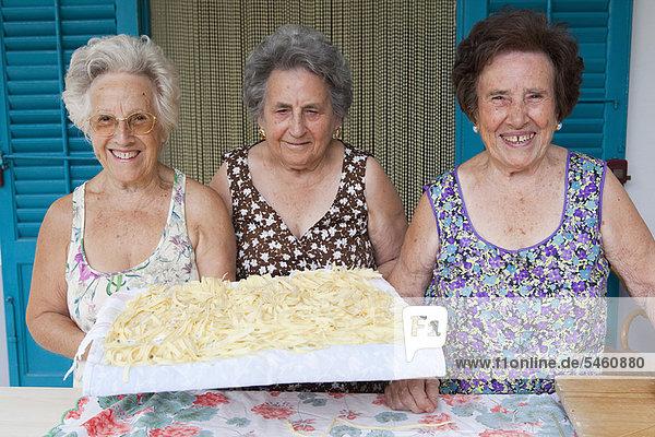 Ältere Frauen mit Nudelkorb Ältere Frauen mit Nudelkorb