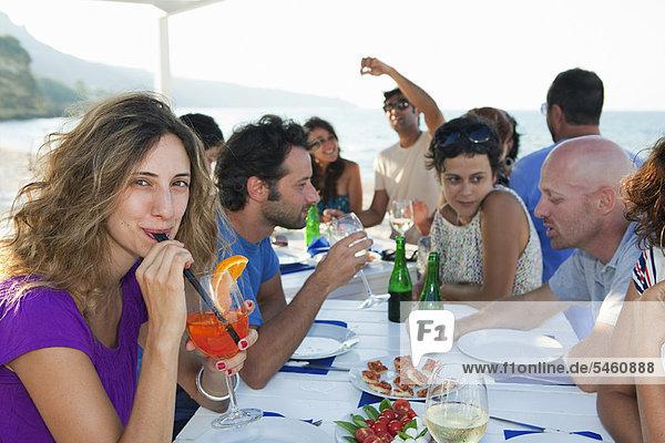 Freunde beim Trinken am Tisch im Freien