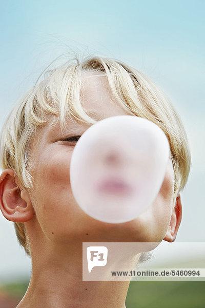 Lächelnder Junge bläst Blase ins Freie