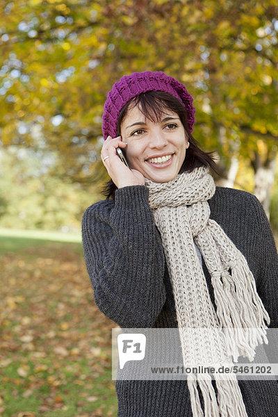 Frau spricht am Handy im Park