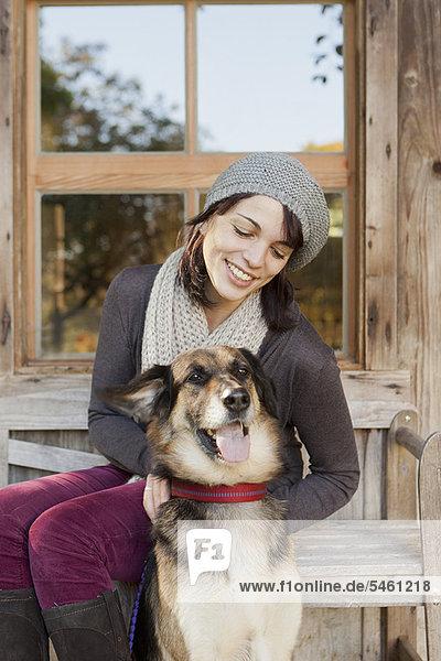 Frau streichelt Hund auf der Veranda