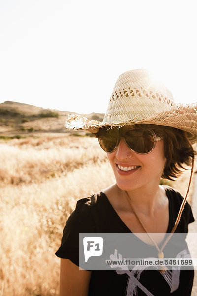 Smiling woman standing in wheatfield 38bsj0207rm