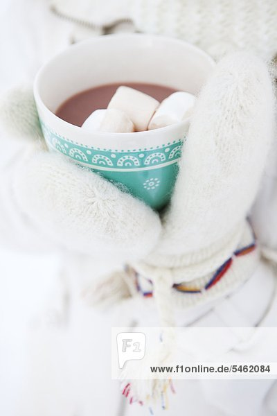 Girls hands in knitted gloves holding hot chocolate with marshmallows