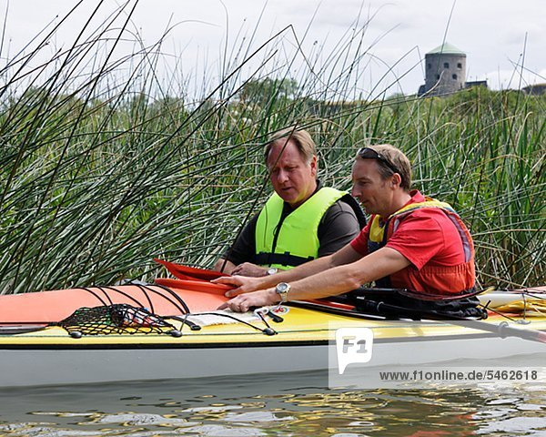 Two men in kayak looking at a map