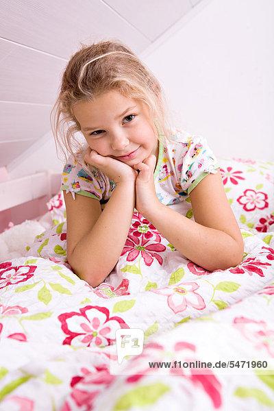Kleines Mädchen beim Aufwachen im Bett