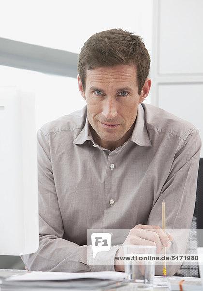 Mann sitzt ernst an Schreibtisch  Blick in die Kamera