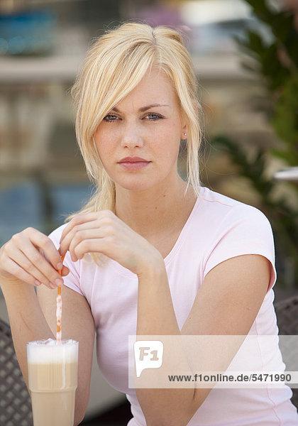Junge Frau sitzt in Bistro und schaut sehr ernst