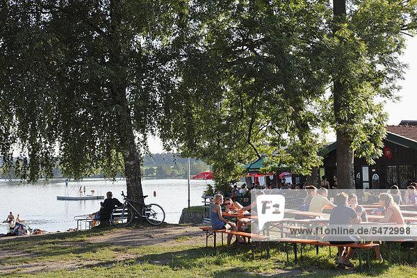 Guests in a beer garden  Strandbad Tengling  Lake Tachinger  Rupertiwinkel  Upper Bavaria  Bavaria  Germany  Europe