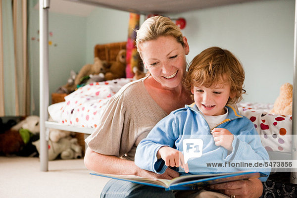 Mother reading a book with her son in his bedroom