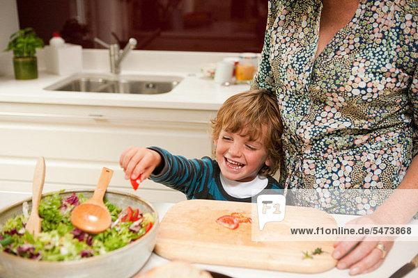 Kleiner Junge  der Mutter hilft  zu Hause gemeinsam Salat zuzubereiten.