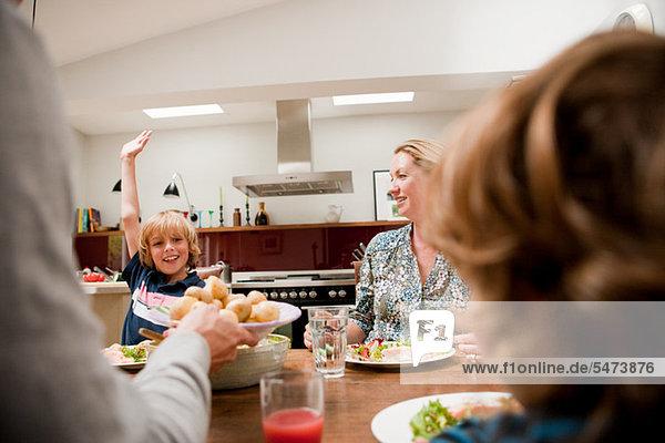 Familie am Esstisch mit Sohn  der den Arm hebt und um mehr Essen bittet.