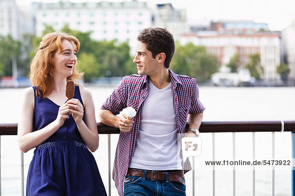 Young couple eating a lolly and an icecream