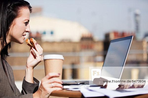 Junge Frau  die draußen einen Laptop benutzt  während sie ein Sandwich isst.